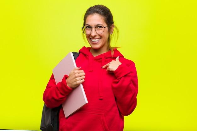 Junger hübscher student, der glücklich, stolz und überrascht schaut und nett auf selbst zeigt, überzeugt und hoch sich fühlt