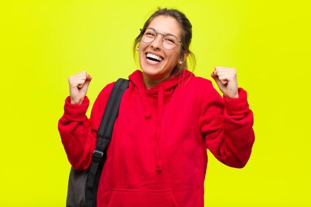 Junger hübscher student, der glücklich, überrascht und stolz sich fühlt, erfolg mit einem großen lächeln schreit und feiert
