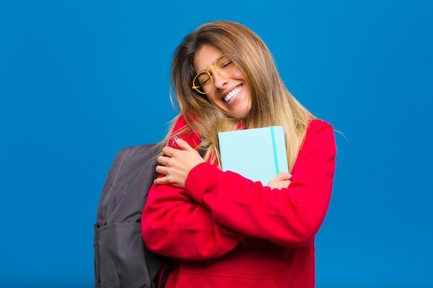 Junger hübscher student, der in der liebe sich fühlt, lächelt, selbst streichelt und umarmt, einzeln bleibt, egoistisch und egozentrisch ist