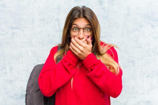 Junger hübscher student, der mund mit den händen mit einem entsetzten, überraschten ausdruck bedeckt, ein geheimnis hält oder oops sagt