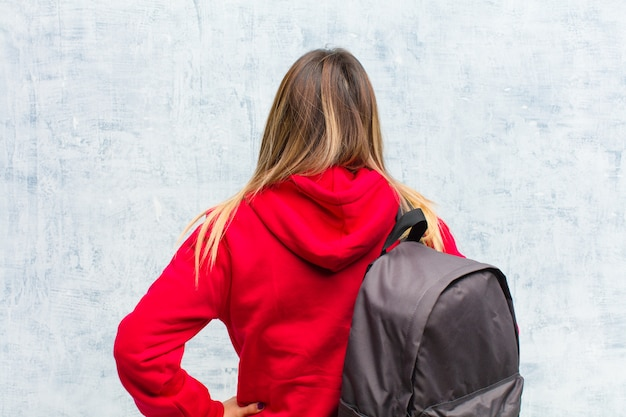 Junger hübscher student, der verwirrt oder voll oder zweifel und fragen sich wundern mit den händen auf hinterer ansicht der hüften glaubt