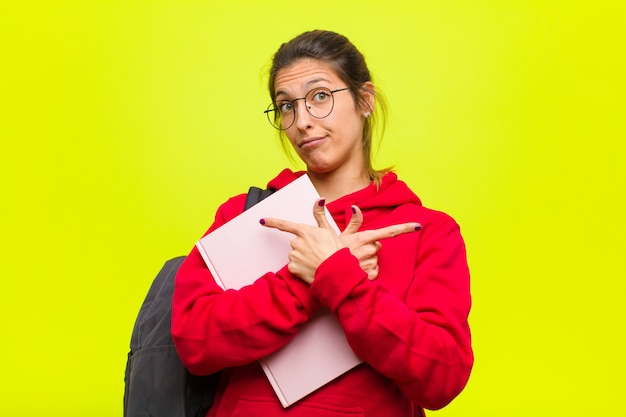 Junger hübscher student, der verwirrt und verwirrt, unsicher schaut und in entgegengesetzte richtungen mit zweifeln zeigt