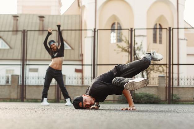 Junger hübscher tänzer, der hiphop tanzt