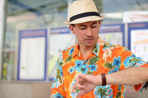 Junger hübscher touristenmann, der wartet und die zeit an der u-bahnstation überprüft