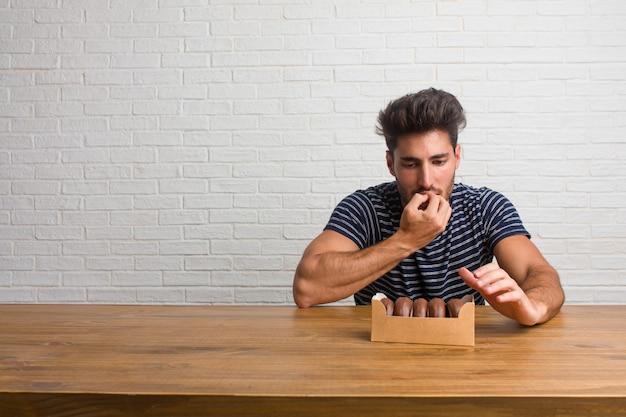 Junger hübscher und natürlicher mann, der auf beißenden nägeln einer tabelle sitzt, nervös und sehr besorgt und erschrocken