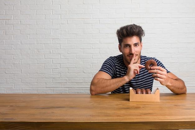Junger hübscher und natürlicher mann, der auf einer tabelle hält ein geheimnis hält oder nach ruhe, ernstes gesicht, gehorsamkonzept fragt. schokoladen donuts essen.