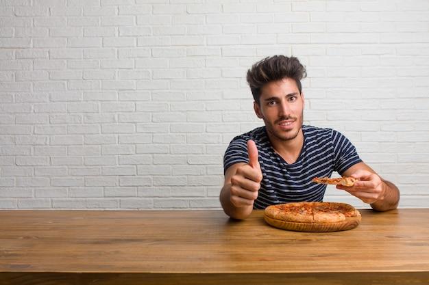 Junger hübscher und natürlicher mann, der auf einer tabelle nett und aufgeregt sitzt, oben ihren daumen, konzept des erfolgs und zustimmung, okaygeste lächelt und anhebt. eine leckere pizza essen.