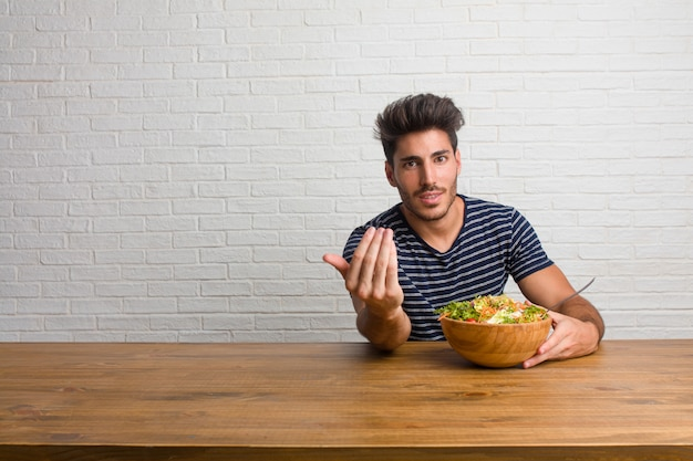 Junger hübscher und natürlicher mann, der auf einer tabelle sitzt, die einlädt, zu kommen, überzeugt und lächelnd, eine geste mit der hand machend und positiv und freundlich seiend. einen frischen salat essen.