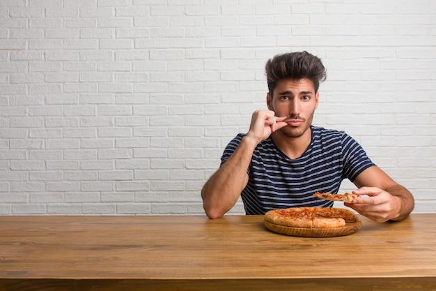 Junger hübscher und natürlicher mann, der auf einer tabelle sitzt und ein geheimnis hält oder um ruhe, ernstes gesicht bittet
