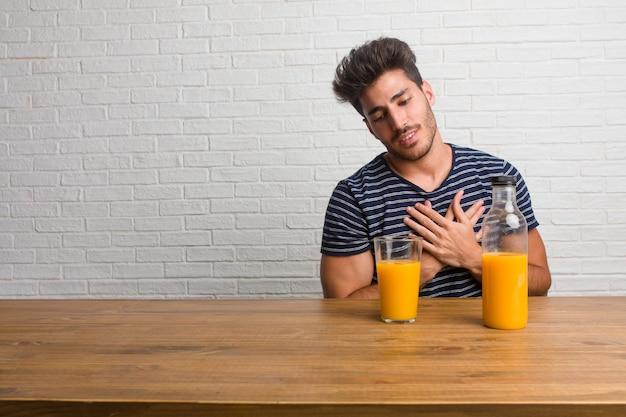 Junger hübscher und natürlicher mann, der auf einer tabelle tut eine romantische geste sitzt
