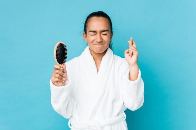 Junger indianer gemischter rasse, der eine haarbürste hält, die finger kreuzt, um glück zu haben