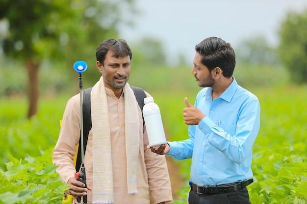 Junger indischer agronom, der dem landwirt eine flüssigdüngerflasche gibt und produktinformationen auf dem grünen landwirtschaftsfeld sagt.