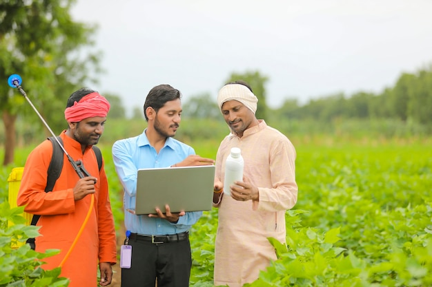 Junger indischer agronom, der dem landwirt eine flüssigdüngerflasche gibt und produktinformationen im laptop auf dem grünen landwirtschaftsfeld zeigt.