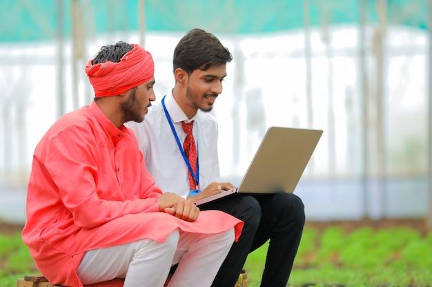 Junger indischer agronom, der landwirt einige informationen im laptop am gewächshaus zeigt