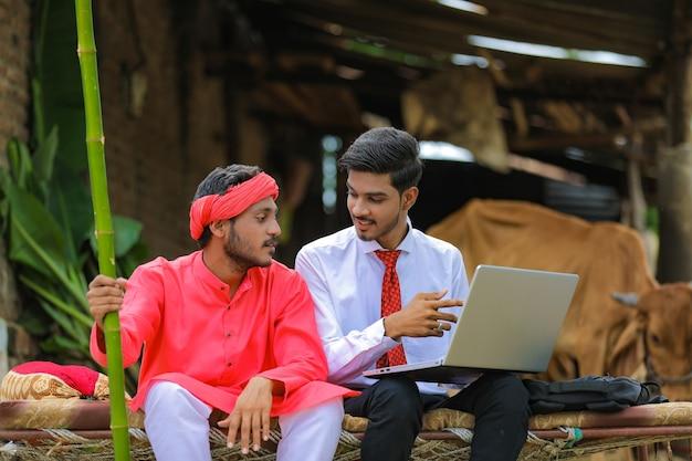 Junger indischer agronom, der landwirt einige informationen in laptop zu hause zeigt