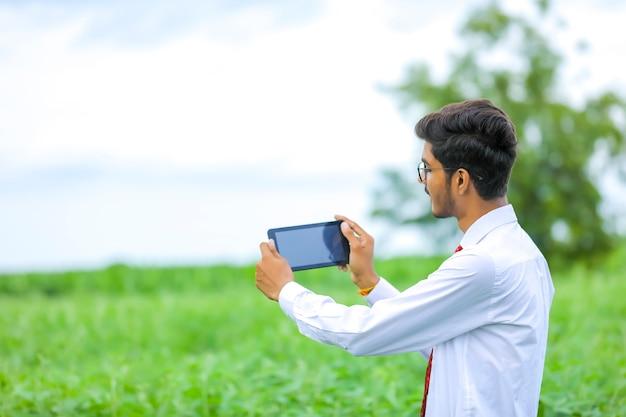 Junger indischer agronom, der smartphone am feld zeigt