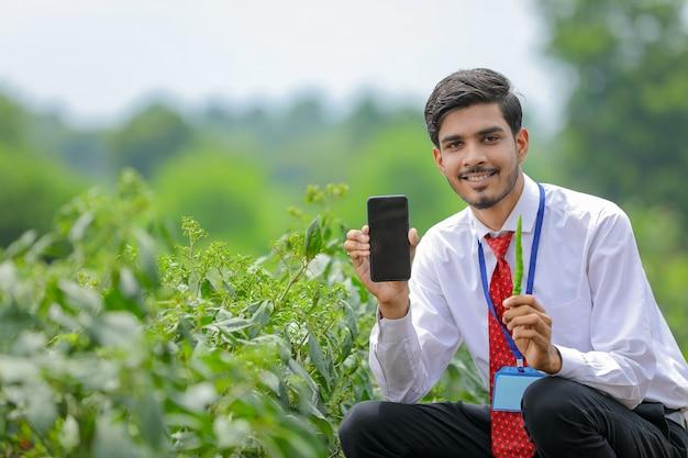 Junger indischer agronom, der smartphone mit landwirt am grünen chilipfefferfeld zeigt