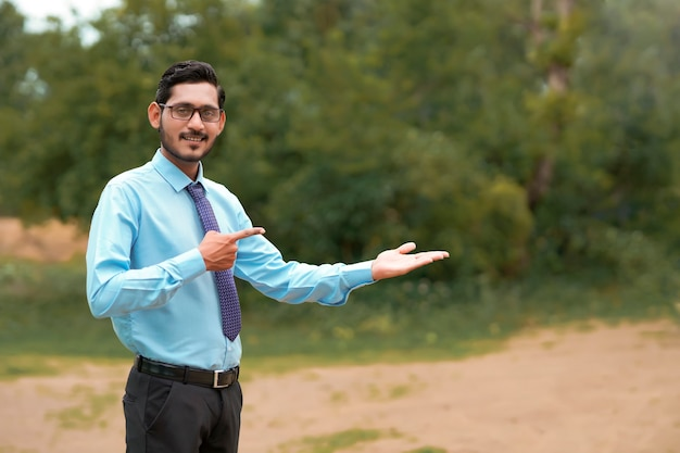 Junger indischer agronom, der über naturhintergrund ausdruck gibt