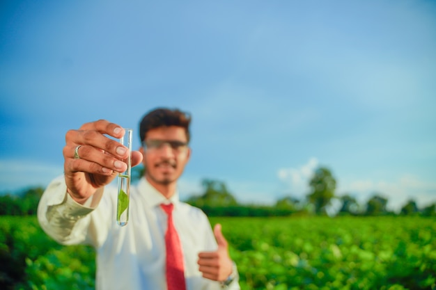 Junger indischer agronom mit reagenzglas, landwirtschafts- und wissenschaftlerkonzept.