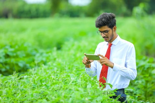 Junger indischer agronom mit smartphone am feld