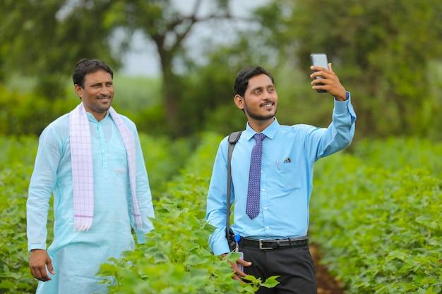 Junger indischer agronom oder banker, der ein selfie mit einem bauern im landwirtschaftsfeld macht