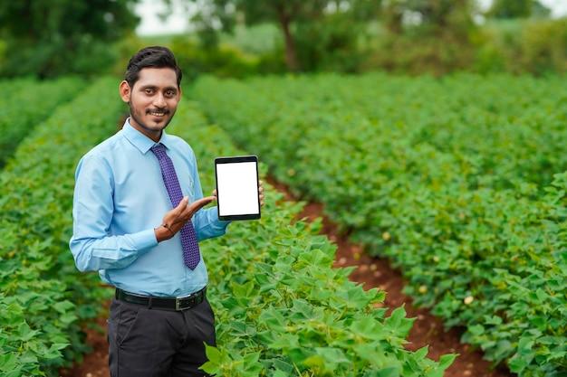 Junger indischer agronomen oder offizier, der tablette am landwirtschaftsfeld zeigt.