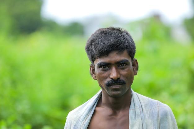 Junger indischer armer mann, der über naturhintergrund steht