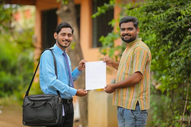 Junger indischer bankbeamter, der papierkram erledigt und dem landwirt ein zertifikat gibt.