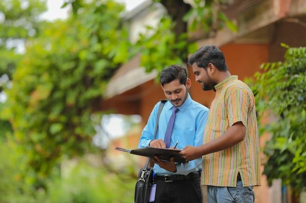 Junger indischer bankbeamter, der papierkram mit landwirt abschließt.
