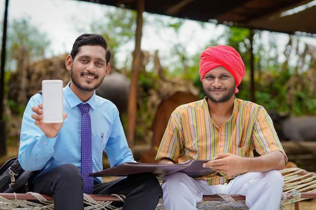 Junger indischer bankbeamter oder agronom, der smartphone mit landwirt auf seiner farm zeigt