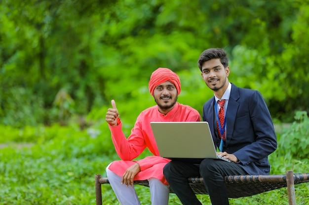 Junger indischer bankier, der dem landwirt einige informationen im laptop am feld zeigt