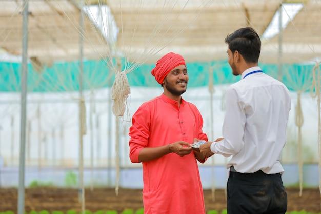 Junger indischer bankier, der landwirt im gewächshaus geld gibt