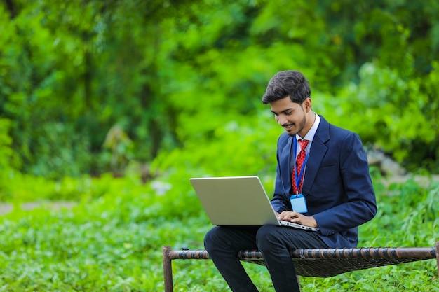 Junger indischer bankier, der laptop am feld verwendet
