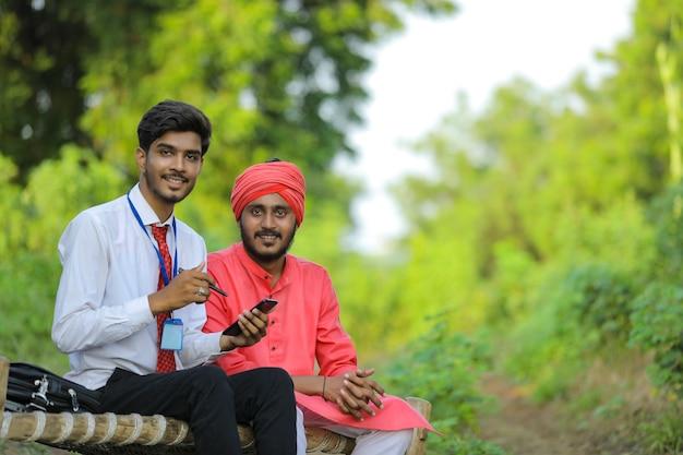 Junger indischer bankier diskutieren mit landwirt am feld