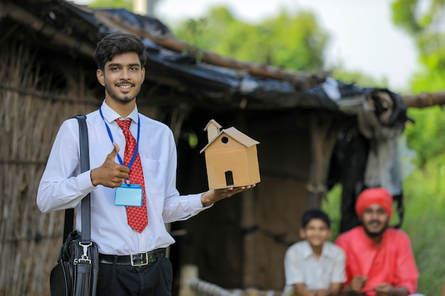 Junger indischer bankier oder agronom besuchen arme bauernfamilie