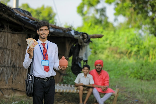 Junger indischer bankier oder agronom, der geld und tonschweinchen zeigt, die in der hand am armen bauernhaus halten