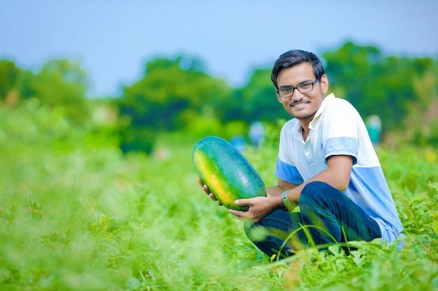 Junger indischer bauer am wassermelonenfeld