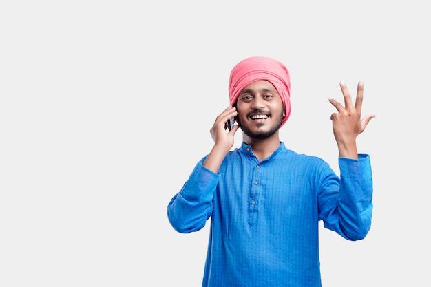 Junger indischer bauer, der am handy über weißem hintergrund spricht.