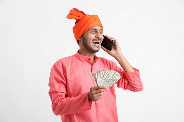 Junger indischer bauer, der auf handy spricht und geld auf weißem hintergrund zeigt.