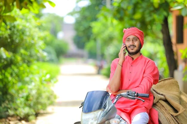 Junger indischer bauer, der auf handy spricht