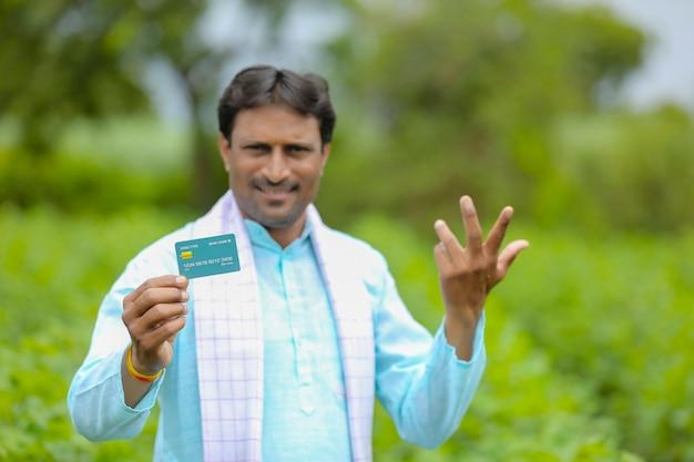 Junger indischer bauer, der debit- oder kreditkarte auf seinem grünen landwirtschaftsfeld zeigt