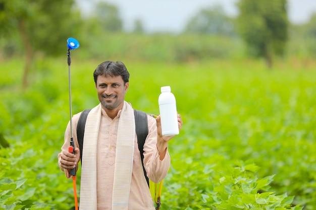 Junger indischer bauer, der flüssigdüngerflasche am landwirtschaftsfeld zeigt.