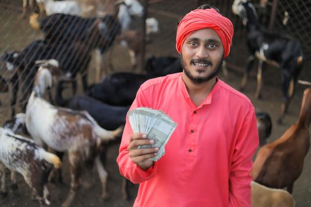 Junger indischer bauer, der geld an ziegenmilchfarm zeigt