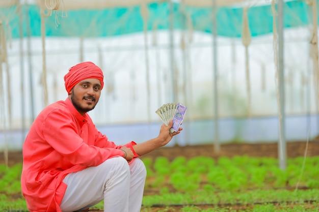 Junger indischer bauer, der geld im gewächshaus oder im polyhaus zählt und zeigt