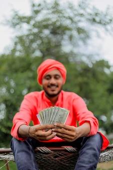 Junger indischer bauer, der geld zählt und zeigt