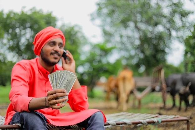 Junger indischer bauer, der geld zeigt und zu hause am handy spricht