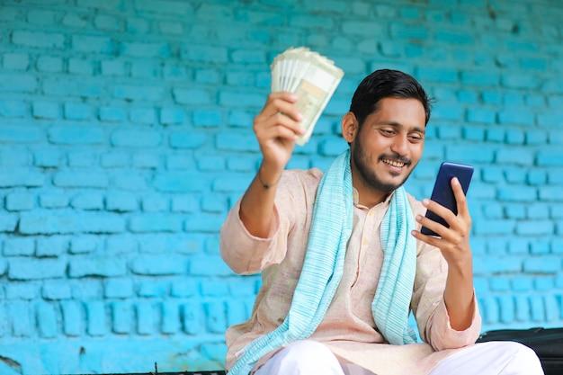 Junger indischer bauer, der geld zeigt und zu hause auf dem handy benutzt