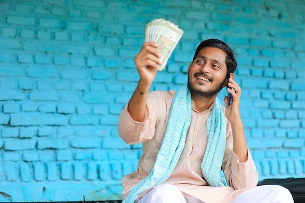 Junger indischer bauer, der geld zeigt und zu hause mit dem handy spricht
