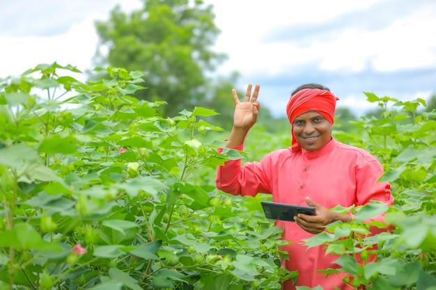 Junger indischer bauer, der handy am landwirtschaftsfeld verwendet