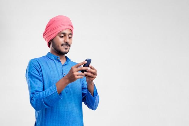 Junger indischer bauer, der handy über weißem hintergrund verwendet.